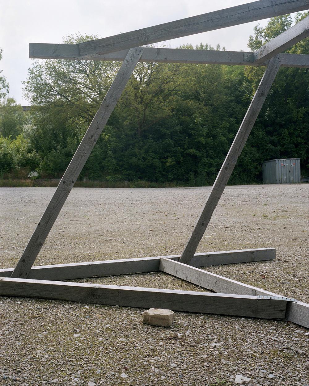 Fragment konstrukcji zdrewna onieregularnym kształcie. Stoi naziemi wysypanej żwirem. Zanią rosną zielone drzewa. Poprawej stronie, stoi garaż zblachy.